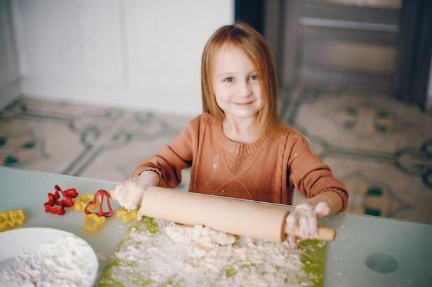 Petite fille cuire la pâte pour les cookies
