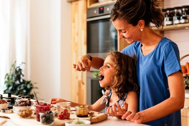 Petite fille cuisinant avec sa mère dans la cuisine. concept de chef infantile.