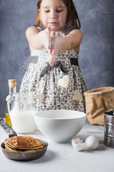 Petite fille cuisine des crêpes avec amour. la magie saute d'un bol en forme de cœur.