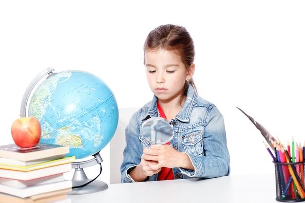 Petite fille curieuse regardant par la loupe sur le globe