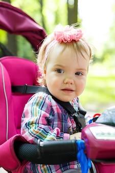 Une petite fille dans un arc sur la tête est assise au volant d'un vélo. le premier vélo pour enfants. balade estivale avec bébé