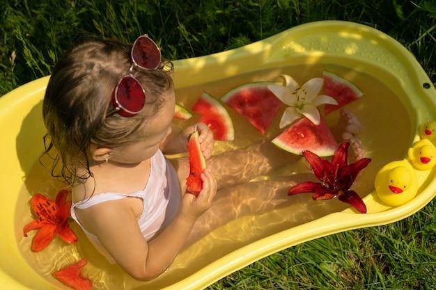 Une petite fille dans un bain jaune avec des fleurs et une pastèque sucrée