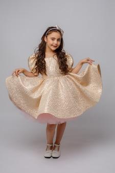 Petite fille dans une belle robe sur fond blanc