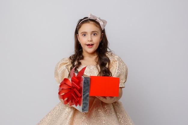 Une petite fille dans une belle robe tient une boîte-cadeau sur fond blanc