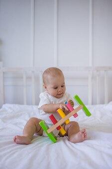 Petite fille dans un body blanc est assise dans un jouet éducatif sur le lit