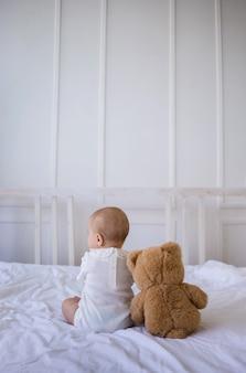 Petite fille dans un body blanc est assise le dos avec un ours en peluche sur une couverture en coton blanc sur le lit dans la chambre