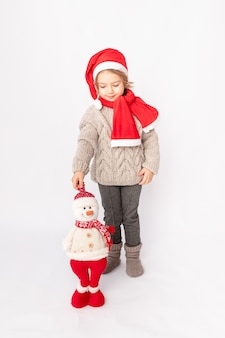 Petite fille dans un bonnet de noel avec un bonhomme de neige sur fond blanc, espace pour le texte