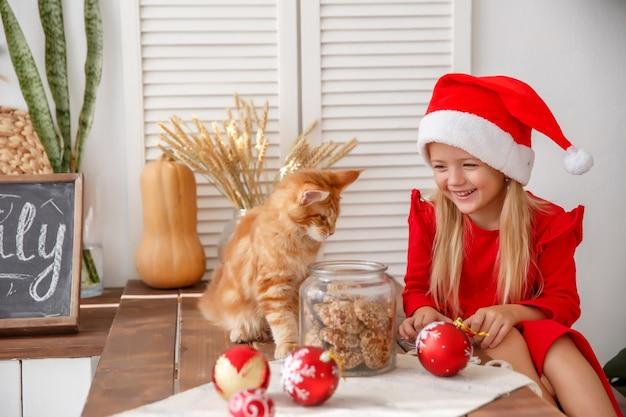 Petite fille dans un bonnet de noel avec un chat dans la cuisine