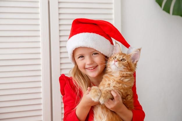 Petite fille dans un bonnet de noel avec un chat