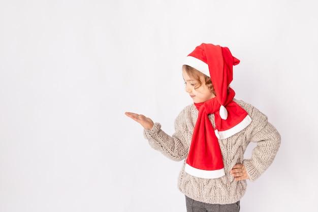 Une petite fille dans un bonnet de noel sur fond blanc tient sa main pour l'espace pour le texte