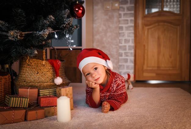 Une petite fille dans un bonnet de noel et un pull rouge regarde une bougie allumée sous l'arbre