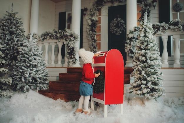 Une petite fille dans un bonnet tricoté blanc fait un vœu et écrit une lettre au père noël et envoie une carte postale par la poste. jette une enveloppe dans la boîte aux lettres
