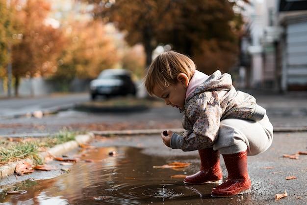 Petite fille dans des bottes de pluie rouges jouant dans une flaque après la pluie