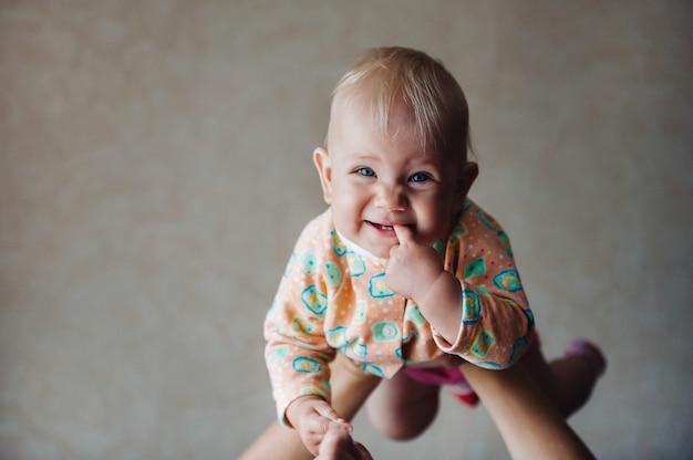 Une petite fille dans les bras de sa mère au-dessus de sa tête sourit avec un doigt dans la bouche.