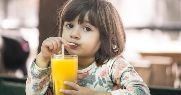 Petite fille dans un café, boire du jus