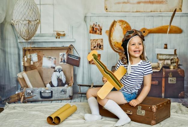 Une petite fille dans une casquette est assise sur une valise rétro et tient un avion en bois dans sa main.