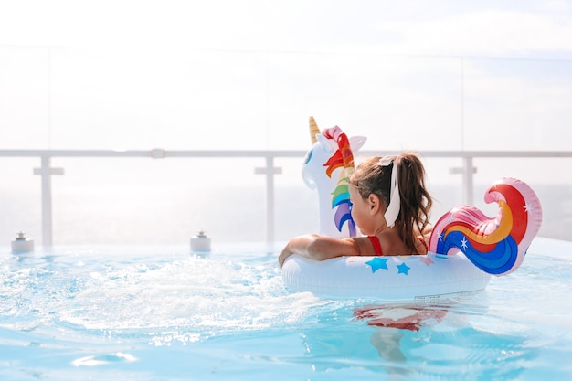 Petite fille dans un cercle de licorne dans une piscine chic sur fond de mer
