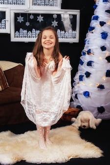 Petite fille dans la chambre avec le sapin de noël. le concept du nouvel an et joyeux noël