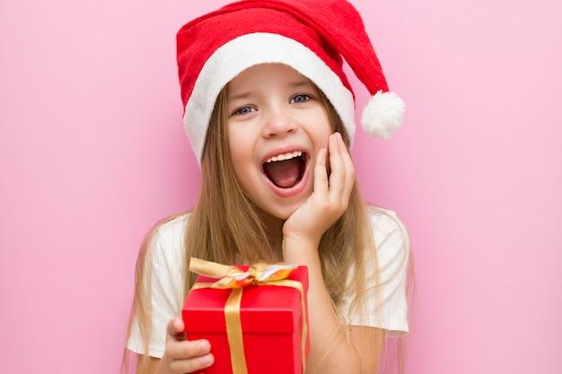 Petite fille dans un chapeau de noël rouge présente une boîte rouge avec un arc en or, un cadeau. des sourires. la nouvelle année est 2021. gros plan