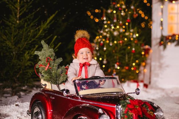 Petite fille dans un chapeau rouge et un manteau avec un arc rouge rit dans une voiture rouge pour enfants