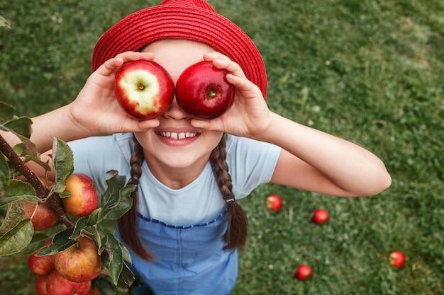 La petite fille dans un chapeau rouge tient deux pommes près des yeux sur un fond d'herbe