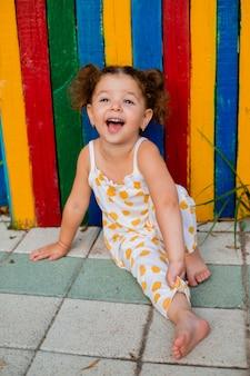Une petite fille dans une combinaison d'été dans une montagne de sourires assis près d'une clôture lumineuse de couleur