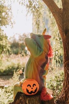 Petite fille dans un costume d'halloween de licorne arc-en-ciel est assise sur une souche au coucher du soleil de la forêt