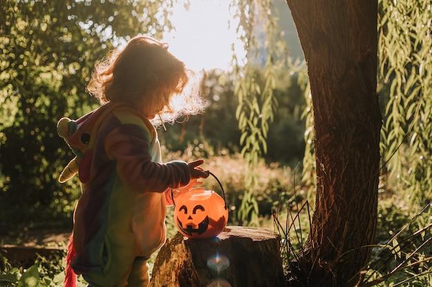 Petite fille dans un costume d'halloween de licorne arc-en-ciel fabuleuse forêt magique merveilleuse