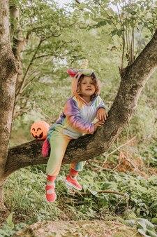 Petite fille dans un costume de licorne arc-en-ciel kigurumi est assise sur un arbre avec un panier de citrouilles pour des bonbons