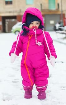 Petite fille dans un costume de neige magenta jouant sur la neige.