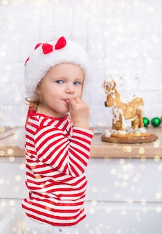 Petite fille dans un costume de noël avec des cadeaux près de l'arbre de noël boit du lait et décore un cerf