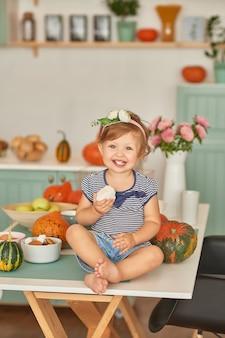 Petite fille dans la cuisine avec des décorations de thanksgiving