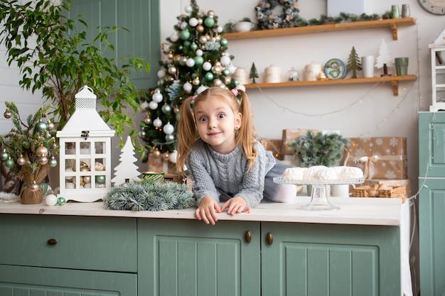 Petite fille dans la cuisine à la maison de noël.