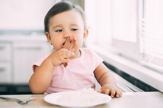 Petite fille dans la cuisine manger des saucisses et purée de pommes de terre