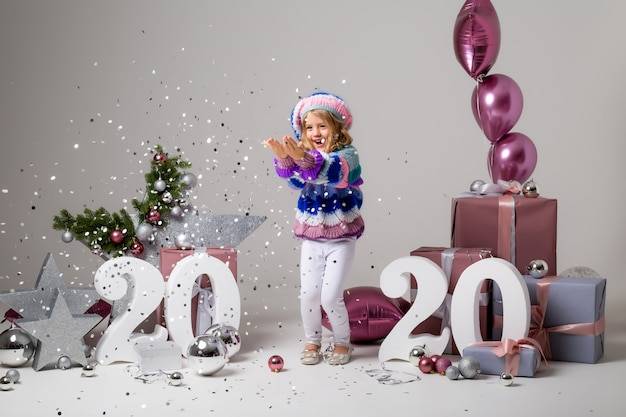 Petite fille dans un décor de vacances à la lumière, coffrets cadeaux, grands nombres 2020, nouvel an et noël