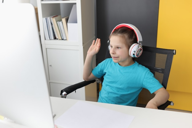 La petite fille dans des écouteurs devant l'ordinateur soulève la leçon dans la salutation