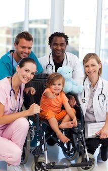 Petite fille dans un fauteuil roulant avec l'équipe médicale
