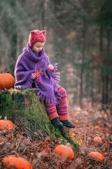 Petite fille dans une forêt d'automne est assise sur une souche moussue dans un costume tricoté et un chapeau avec des oreilles de chanterelle à côté de citrouilles et regarde les baies rouges sur une branche