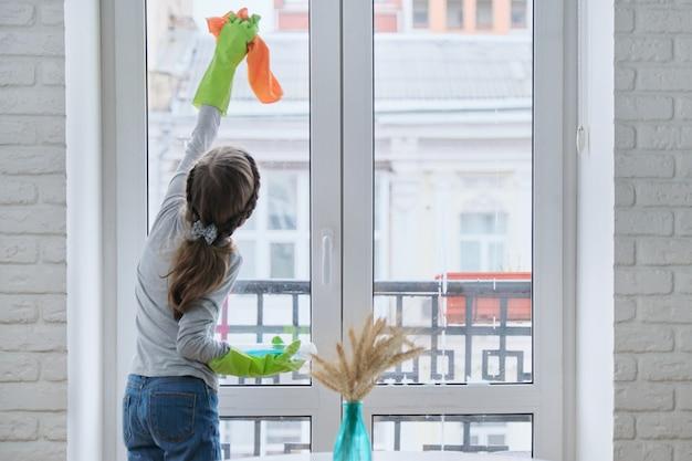 Petite fille dans des gants avec un détergent en spray avec chiffon de nettoyage des fenêtres