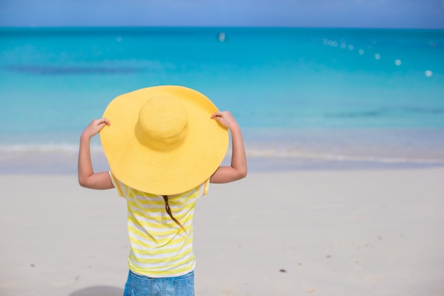 Petite fille dans un grand chapeau de paille jaune sur la plage de sable blanc