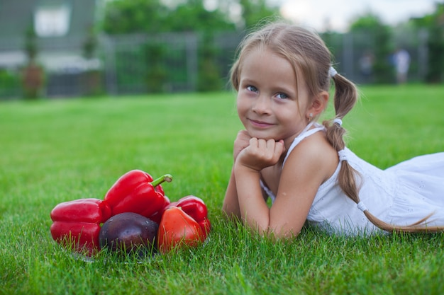 Petite fille dans le jardin avec une assiette de légumes