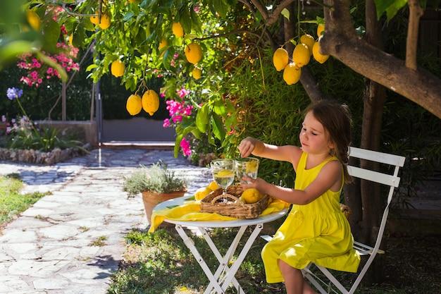 Petite fille dans le jardin assis à une table sous un arbre boit de la limonade. antibes, france