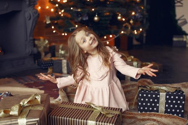 Petite fille dans une jolie robe près de l'arbre de noël avec présent