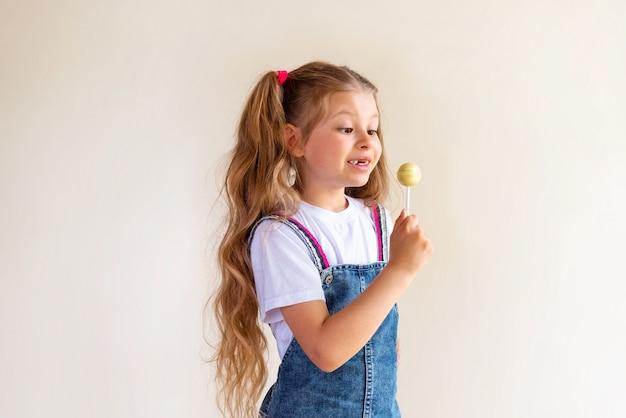 Une petite fille dans une jupe en jean tient une sucette