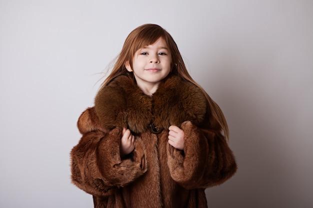Petite fille dans le long manteau brun de ma mère