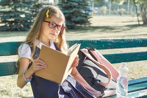 Petite fille dans des lunettes d'uniforme scolaire, avec sac à dos, bouteille d'eau, livre de lecture