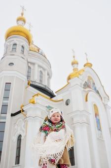 Une petite fille dans un manteau de fourrure et un foulard russe à la surface d'une église orthodoxe