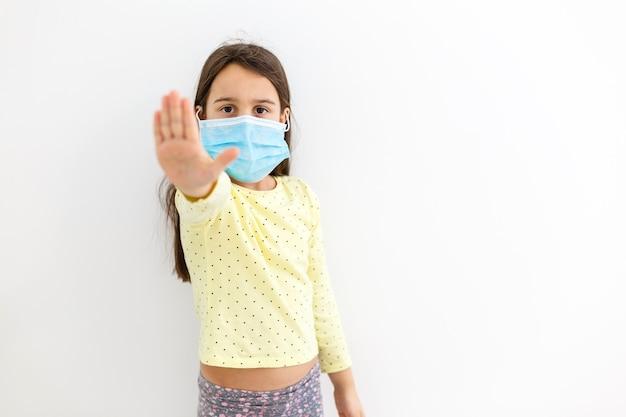 Petite fille dans un masque jetable sur fond clair. protection contre l'épidémie de virus corona