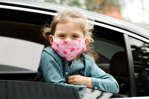 Petite fille dans un masque médical est assise dans un siège enfant dans la voiture.