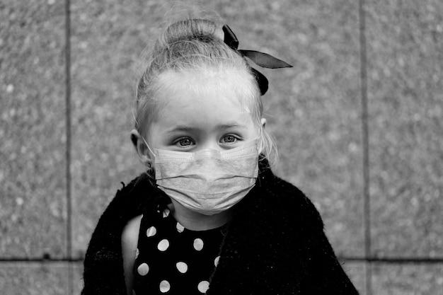 Petite fille dans un masque de protection. photo en noir et blanc